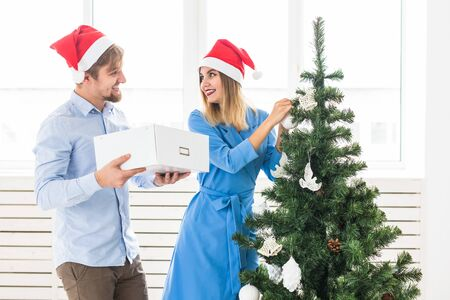 Holidays and festive concept - Young family couple decorating the christmas tree
