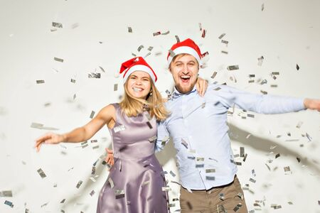 New year, christmas and party concept - Cheerful young people showered with confetti on a white background.
