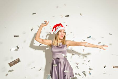 New year and holidays concept - Happy excited young woman in santa claus hat dancing and laughing over white background. 스톡 콘텐츠