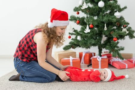 Holidays and Christmas concept - young mother with baby santa claus in front of xmas tree Stock fotó
