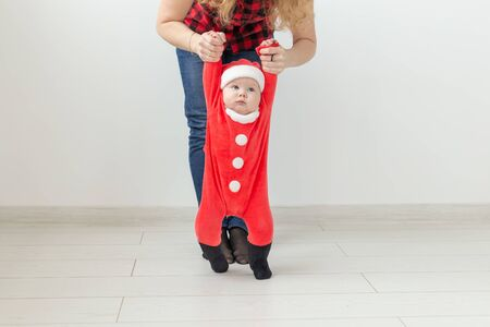 Children, childhood and holidays concept - baby in christmas clothes making first steps Stock Photo