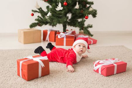 Cute baby girl wearing santa claus suit crawling on floor over Christmas tree. Holiday season. Reklamní fotografie
