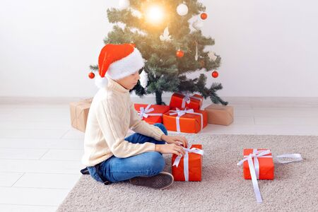 Holidays, christmas, childhood and people concept - smiling happy teen boy in santa hat opens gift box over christmas tree background