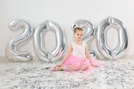 New year, holidays and celebration concept - Little girl sitting near with numbers balloons 2020