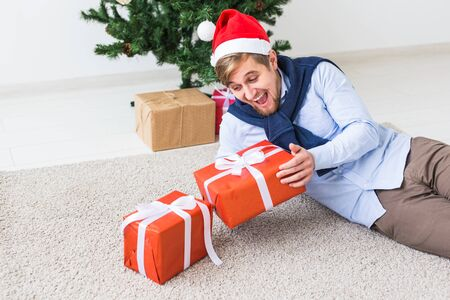 Christmas and holidays concept - Happy man in santa hat opening a gift at home in the living room