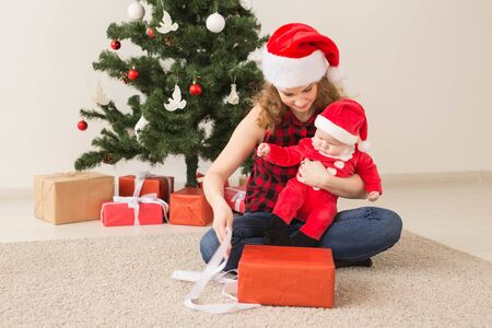 Family, childhood and Christmas concept - Portrait of happy mother and adorable baby in suit of Santa