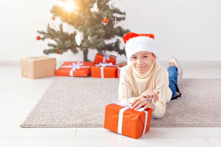 Holidays, christmas, childhood and people concept - smiling happy teen boy in santa hat with gift box over christmas tree background 写真素材