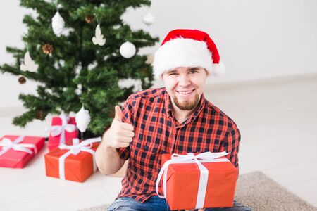 Christmas and holidays concept - Funny man in santa hat holding a gift at home in the living room