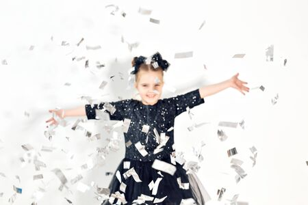 Concepto de fiesta, vacaciones, año nuevo y celebración - Niña lanzando confeti.