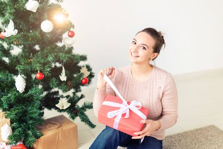 christmas, x-mas, winter, happiness concept - girl opens a gift against the background of the Christmas tree. Happy young woman celebrating Christmas