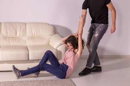 Domestic violence, abuse and victim concept - man and woman having fight, man dragging helpless woman by hair