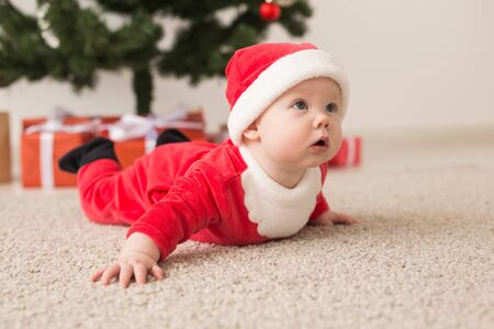 Cute baby girl wearing santa claus suit crawling on floor over Christmas tree. Holiday season.