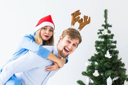 Funny man giving piggyback to his wife while they wearing Santa hats for Christmas holidays at home. Foto de archivo - 134782062