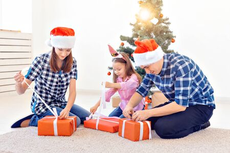 Holidays and presents concept - Portrait of a happy family opening gifts at Christmas time