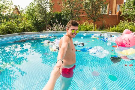 Ecology, plastic trash, environmental emergency and water pollution - guy lead in a pool with garbage