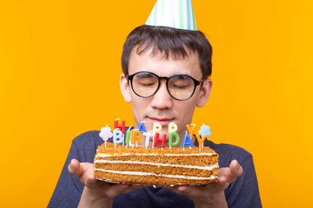 Portrait of a funny positive guy with a paper cap and glasses holding a congratulatory homemade cake in his hands on a yellow background. Concept and fun and celebration.
