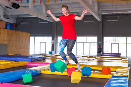 Fitness, fun, leisure and sport activity concept - Young happy woman jumping on a trampoline indoors