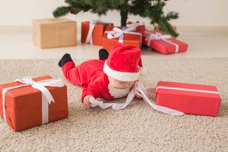 Beautiful little baby celebrates Christmas. New Years holidays. Baby in a Christmas costume and in santa hat and gift box, top view. Stock Photo