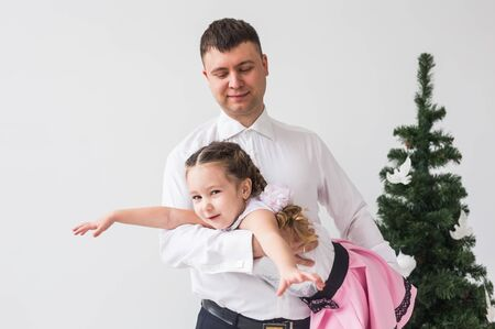 Children, festive and holidays concept - Father and daughter having fun near christmas tree Banque d'images - 135503402