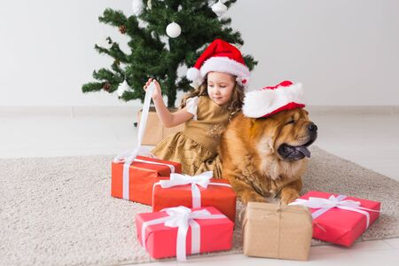 Children and pet concept - Cute girl with chow dog sitting near the Christmas tree. Merry Christmas and Happy Holidays. Banque d'images - 135503802