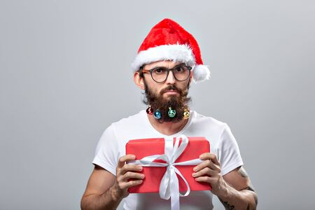 Christmas, holidays, barbershop and style concept - young handsome bearded santa claus man with many small christmas baubles in long beard Banque d'images - 135503590