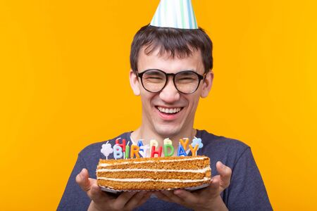 Crazy cheerful young asian guy with glasses holding a burning candle in his hands and a congratulatory homemade cake on a yellow background. Birthday and anniversary celebration concept.