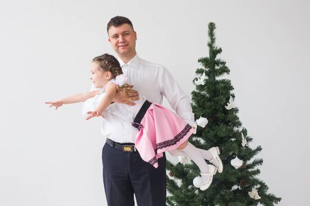 Children, festive and holidays concept - Father and daughter having fun near christmas tree Stock Photo