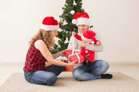 Happy couple with baby celebrating Christmas together at home.