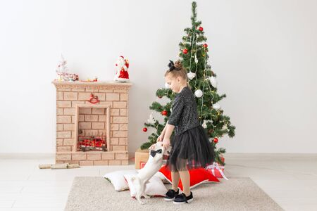 Pets, holidays and Christmas concept - Child girl playing with puppy Jack Russell Terrier near christmas tree Stock Photo