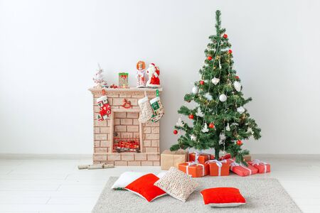 Fireplace and Christmas tree with presents in living room.