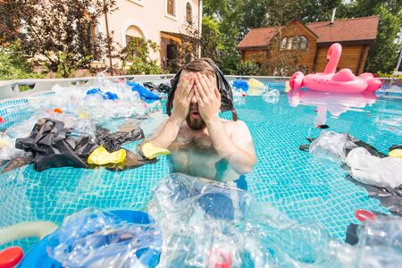 Ecology, plastic trash, environmental emergency and water pollution - shocked man swim in a dirty swimming pool. Фото со стока