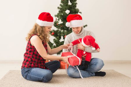 Holidays, children and family concept - Happy couple with baby celebrating Christmas together at home.