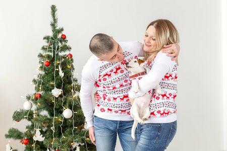 Holidays concept - happy man and woman at christmas tree at home