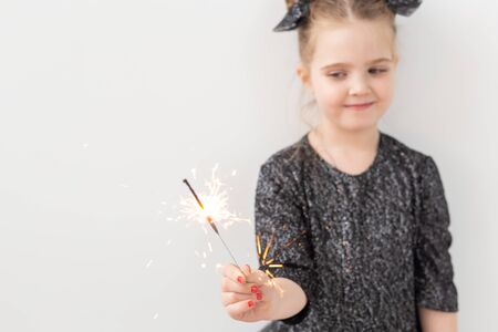 Holidays, christmas and new year concept - Happy child holds burning sparkler in her hand over white background with copy space