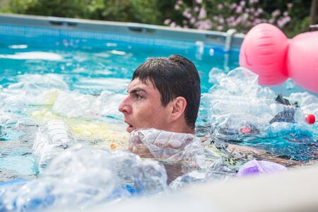 Ecology, plastic trash, environmental emergency and water pollution - shocked man swim in a dirty swimming pool