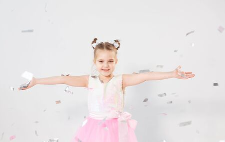 Party, holidays, birthday, new year and celebration concept - Cute child throwing confetti. Standard-Bild