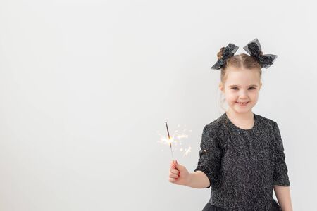 Holidays, christmas and new year concept - Happy child holds burning sparkler in her hand over white background
