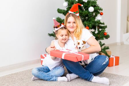 Happy mother with her daughter and jack russell terrier dog sitting near the Christmas tree