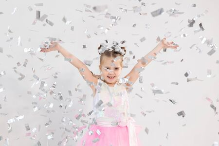 Party, holidays, birthday, new year and celebration concept - Cute child throwing confetti.