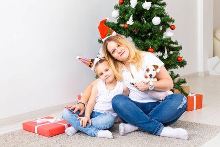 有她的女儿和杰克罗素狗狗的愉快的母亲坐在圣诞树附近