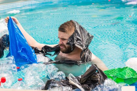 Ecology, plastic trash, environmental emergency and water pollution - shocked man swim in a dirty swimming pool.