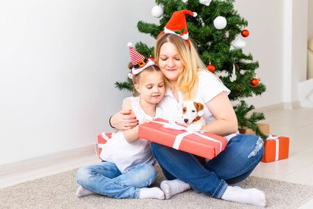 Happy mother with her daughter and jack russell terrier dog sitting near the Christmas tree Banco de Imagens