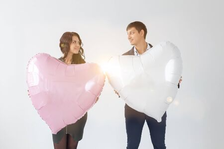 Beautiful young couple with hearts shape air balloons on white background. Valentines Day. Symbol of love Stock Photo - 137162838