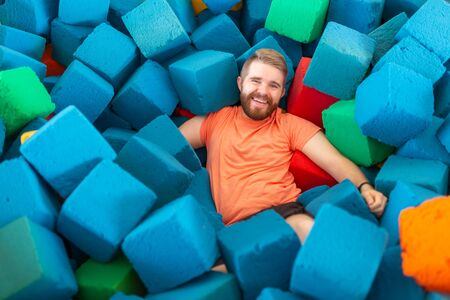 Fitness, fun, leisure and sport activity concept - Funny happy man having fun on a trampoline indoors Banco de Imagens