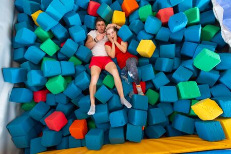 Fitness, fun, leisure and sport activity concept - Funny happy man and woman having fun on a trampoline indoors