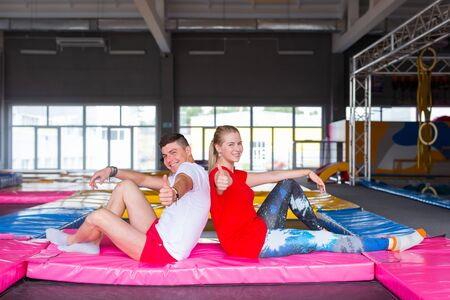 Fitness, fun, leisure and sport activity concept - Happy cheerful couple sits together on a trampoline indoors