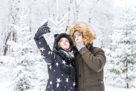 Season, love, technology and leisure concept - happy couple taking selfie by smartphone over winter background