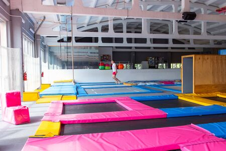 Fitness, fun, leisure and sport activity concept - Handsome happy man jumping on a trampoline indoors