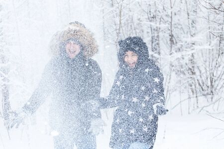 Love, relationship, season and friendship concept - man and woman having fun and playing with snow in winter forest