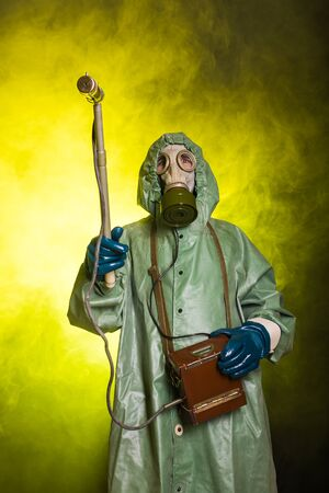 Radiation, pollution and danger concept - Man in protective clothing and a gas mask on a dark background